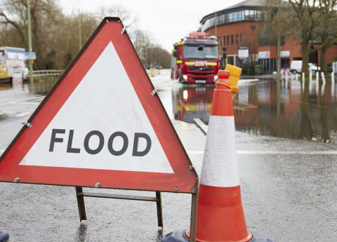 Warning Traffic Sign On Flooded Road With Fire Engine