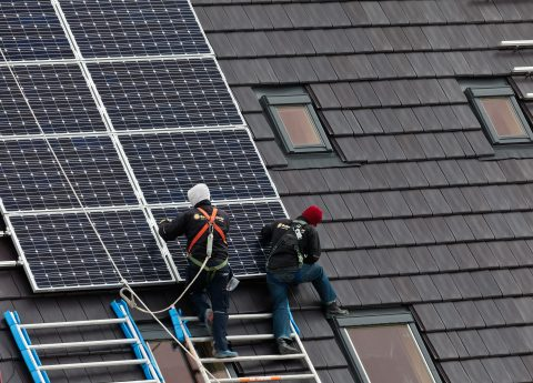 """Heerhugowaard, The Netherlands - April 26, 2012: Construction workers installing solar panels on a roof"""